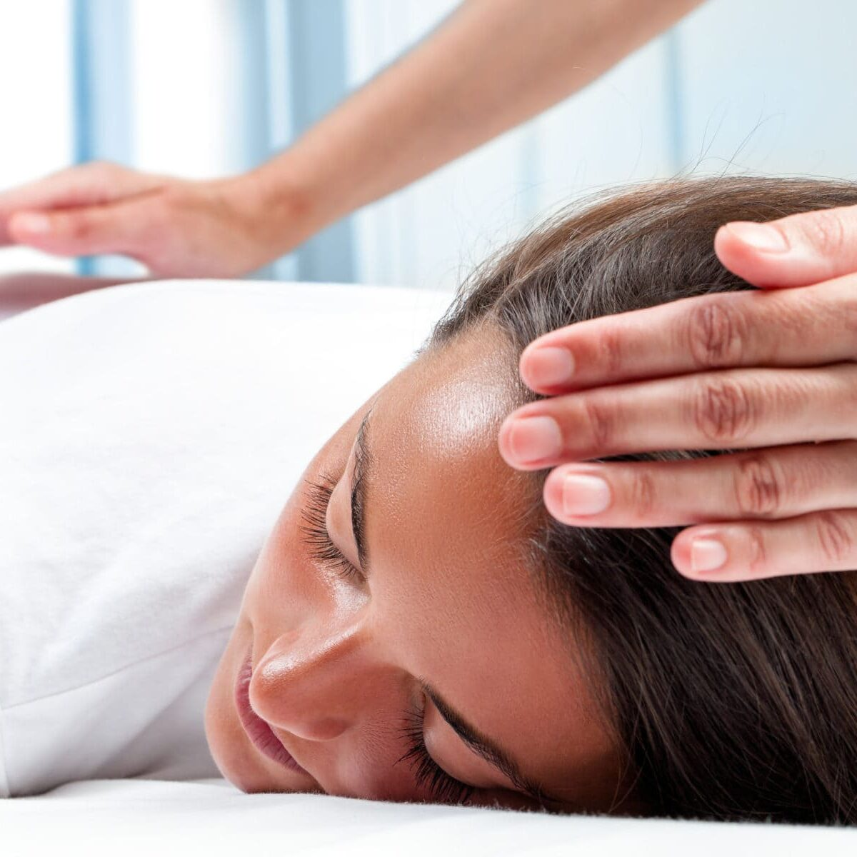 Therapists hands doing reiki therapy on girl. One hand on head and one hand on back.